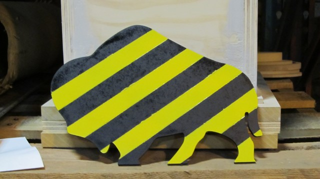 A silhouette of a buffalo, cut out of quarter-inch MDF, then painted with black and yellow caution stripes.