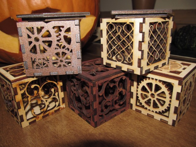 A family of 5 two-inch square wooden boxes featuring gears, vines and Celtic knots