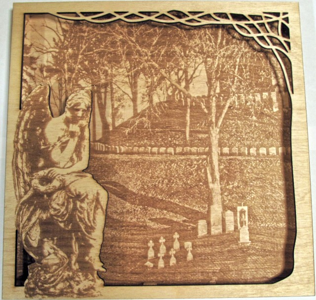 This is a laser cut wall hanging.  The back piece is an image of a hill in a graveyard and the top piece is a part of a tree with an angel statue on the opposite side.