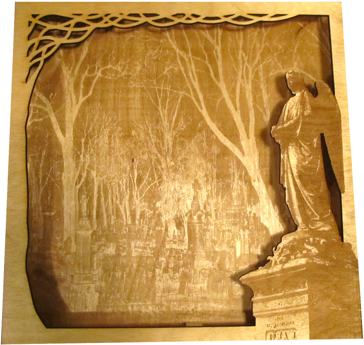 A laser cut piece, one stacked on top of the other for depth. The top piece is a cut out featuring an angelic grave stone and the back piece is a picture of a graveyard with some well defined trees.