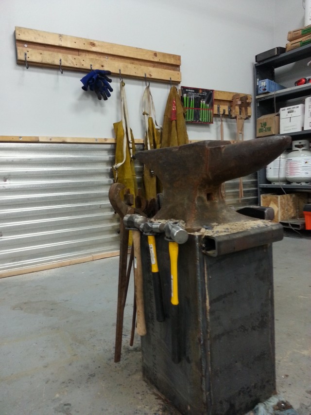 An image of an anvil with hooks in the background