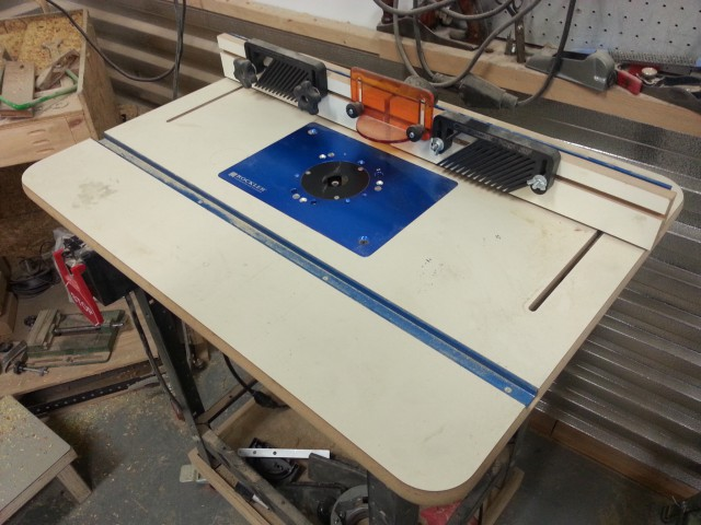 A tight picture of the top of the router table showing slots for clamping  jigs, fence, and anti-kickback devices.