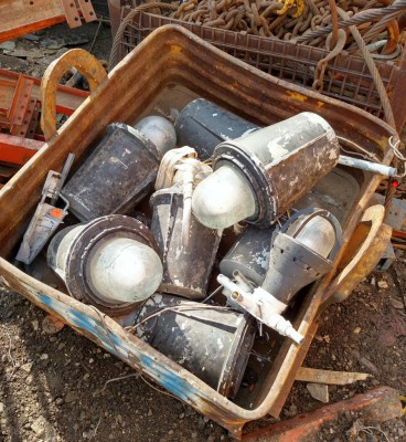 A pallet full of explosion proof lamps at the scrap yard.